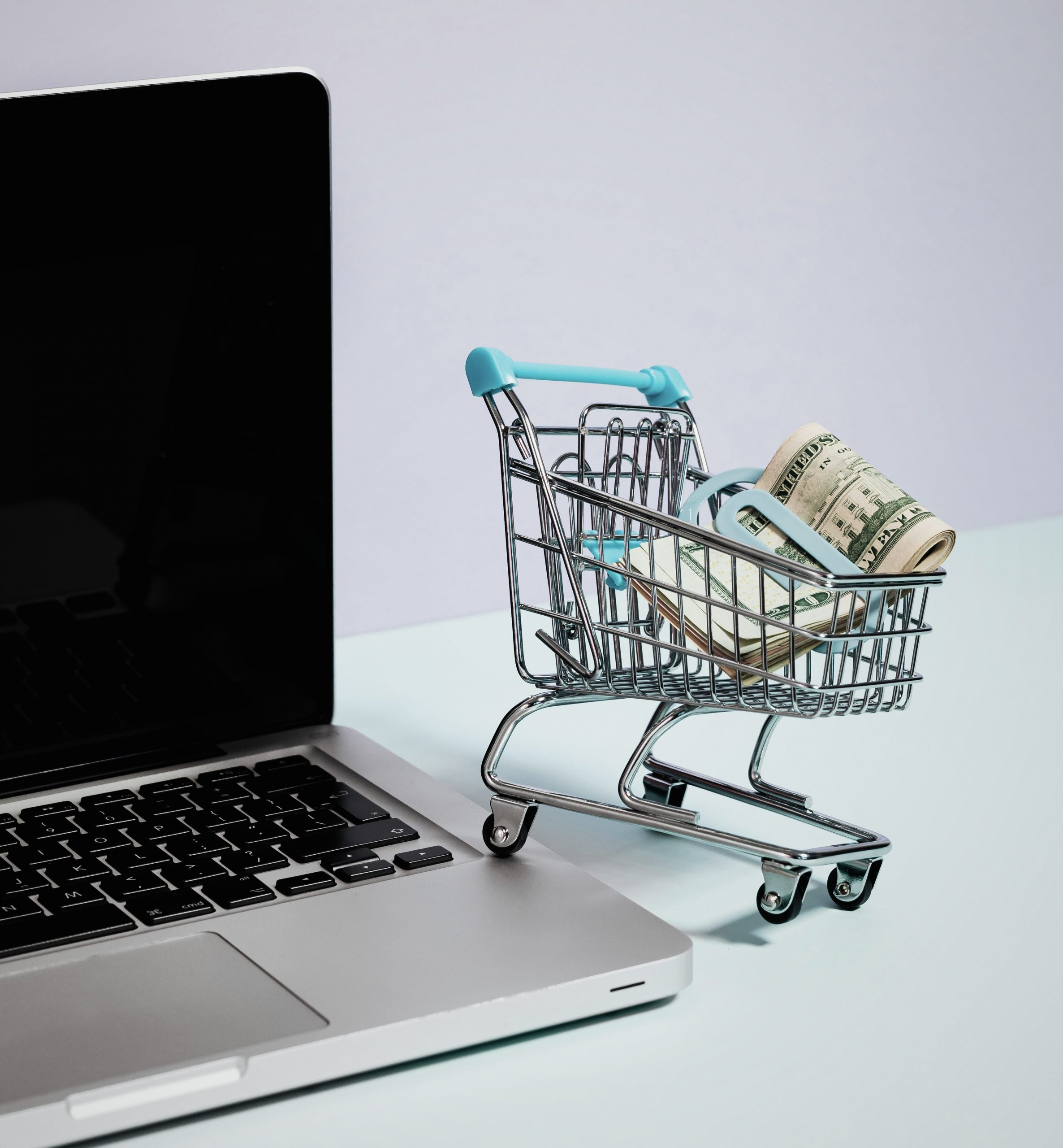 A laptop and and a mini-basket with money